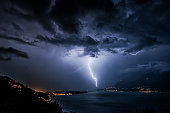 Heavy thunderstorm with bright lightning over Lago Maggiore in Ticino, Switzerland, at night with illuminated cityscapes.