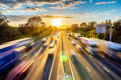 heavy traffic moving at speed on UK motorway in England at sunset.