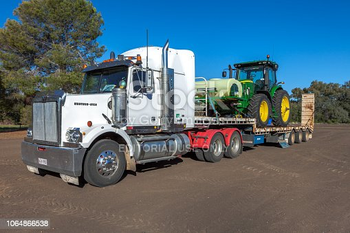 Moree, Australia - April 10, 2017: A low loader heavy transport truck with a farm tractor loaded for shipping in Moree, New South Wales, Australia.