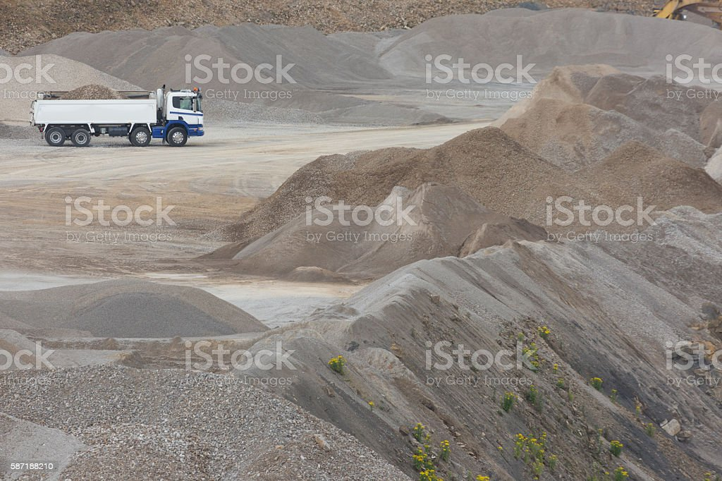heavy transport vehicle driving in a rock and gravel quarry stock photo