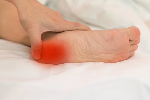istock Heel Pain or plantar fasciitis concept. Hand on foot as suffer from inflammation feet problem of Sever's Disease or calcaneal apophysitis. 1071940472