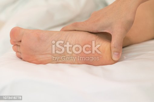 istock Heel Pain or plantar fasciitis concept. Hand on foot as suffer from inflammation feet problem of Sever's Disease or calcaneal apophysitis. 1073416778