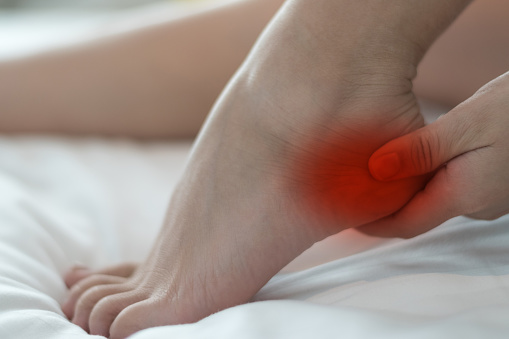 istock Heel Pain or plantar fasciitis concept. Hand on foot as suffer from inflammation feet problem of Sever's Disease or calcaneal apophysitis. 1073416780