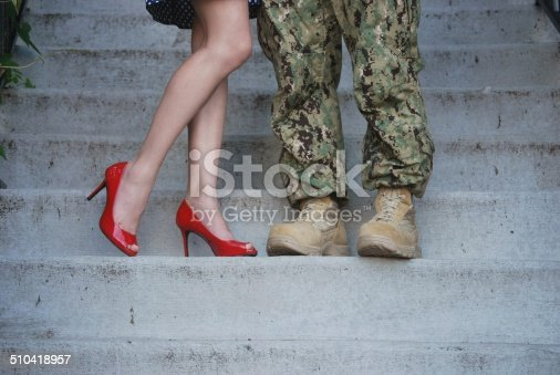 Woman in red high heels, by her husband in combat boots