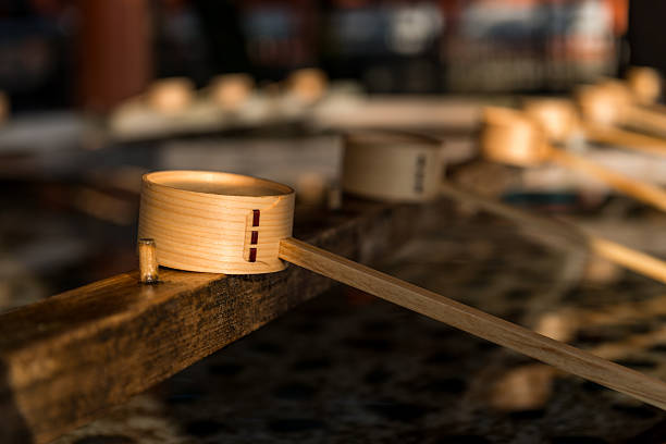 Heian Shrine Kyoto, Japan  - December 31, 2014: Wooden dippers along the chozuya at Heian Shrine in Kyoto, Japan. Worshippers purify their hands and mouths with the water before entering the shrine. shinto shrine stock pictures, royalty-free photos & images