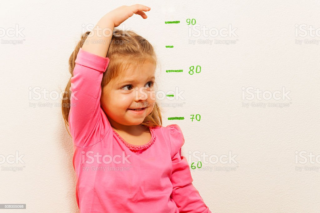 Height measurement by little girl at the wall stock photo