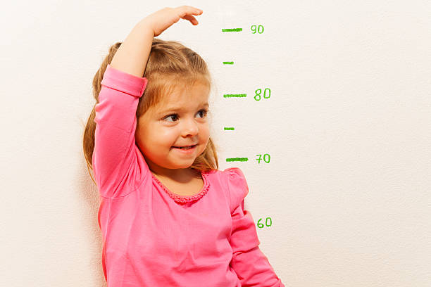 height measurement by little girl at the wall - height measurement stock photos and pictures