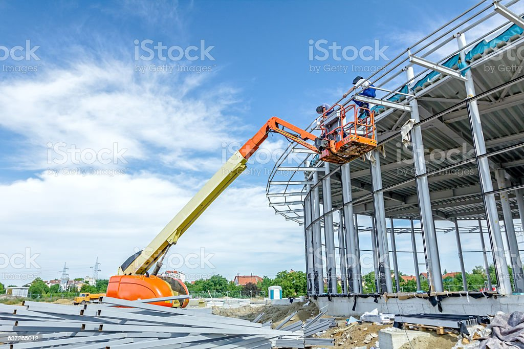 Height workers with help of cherry picker are working. stock photo