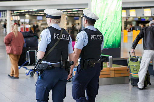 Frankfurt, Germany - November 18, 2015: German police officers with machine gun and bullet proof vests patrol inside the departure terminal of Frankfurt International Airport. Police remained in a heightened state of alert after the Paris terror attacks