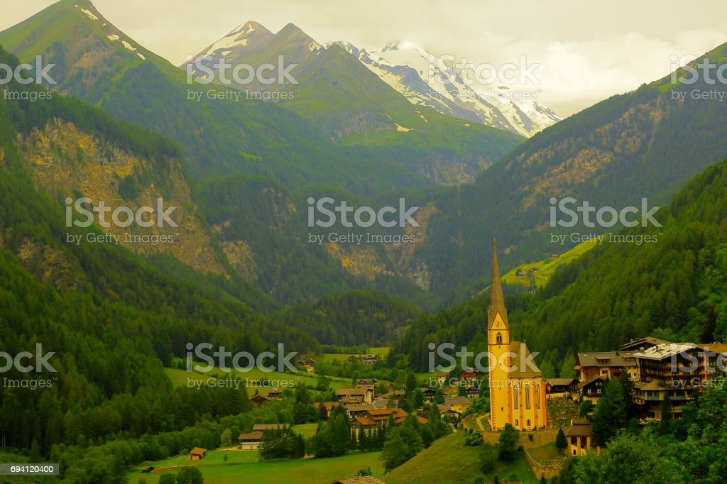 Heiligenblut gothic church village and Hohe Tauern Snowcapped Austrian mountain range - Tirol Alps dramatic landscape and Grossglockner Massif stock photo