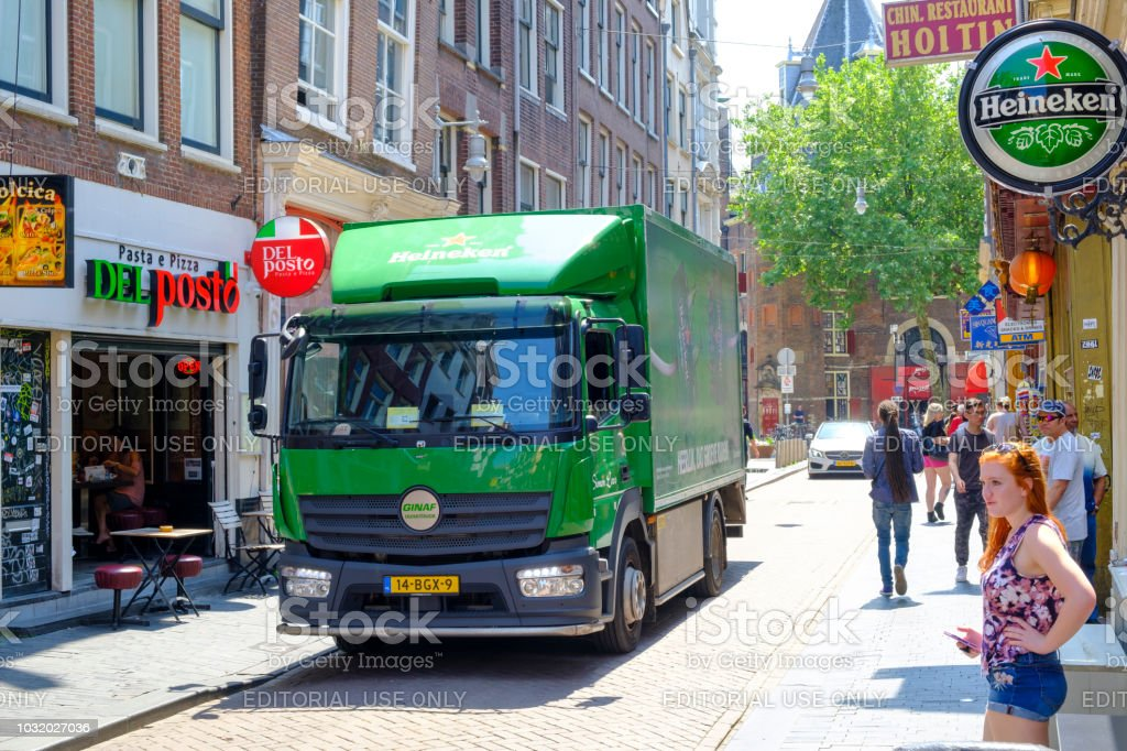 Heineken beer electric delivery truck bringing beer to bars in the narrow streets of the city center in Amsterdam stock photo