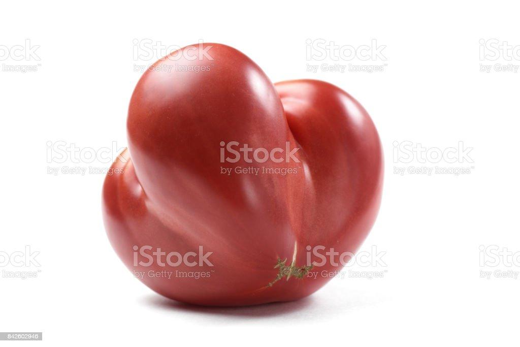 Heirloom fresh juicy red tomato irregular in shape isolated stock photo