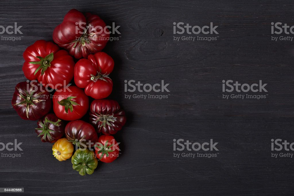 heirloom tomatoes on wooden black board stock photo