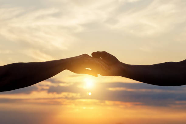 Held hands in the background of the sun . stock photo