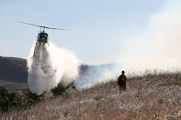 Helicopter and firefighter A helicopter drops water onto a brush fire while a  firefighter watches smoke jumper stock pictures, royalty-free photos & images