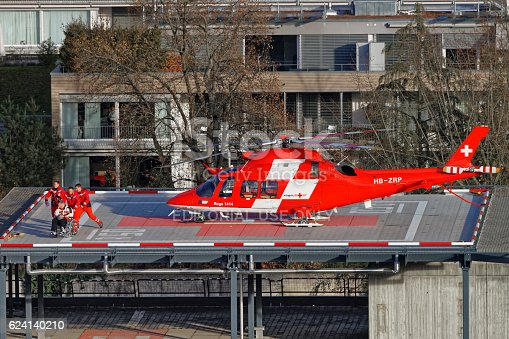 Thun, Switzerland - January 1, 2014: Helicopter and patient on the hospital roof in Thun City. Thun is a city in the canton of Bern in Switzerland. There is a view of Bernese Alps.