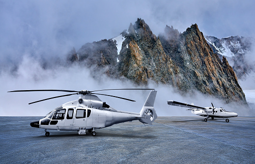 Helicopter and propeller airplane on parking apron at snow-capped mountains backgrounds.