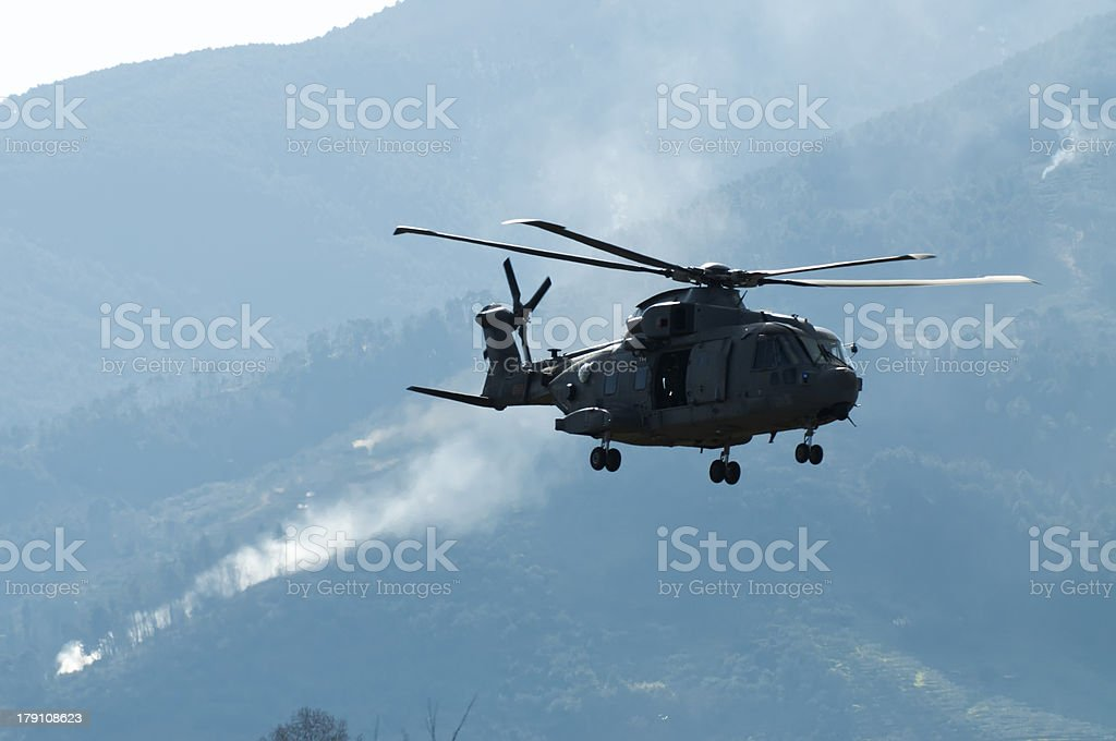 Helicopter and smoke in the distance royalty-free stock photo