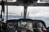 Helicopter cabin with pilots flying over Faroe Islands. Denmark