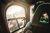 Helicopter cockpit interior with rear view of unrecognizable men co-pilot, flying high up altitude over Mont Blanc massif in French Alps mountains at sunset. The men is unrecognizable and looking through window the amazing nature landscape. All brands from flying instruments were removed.