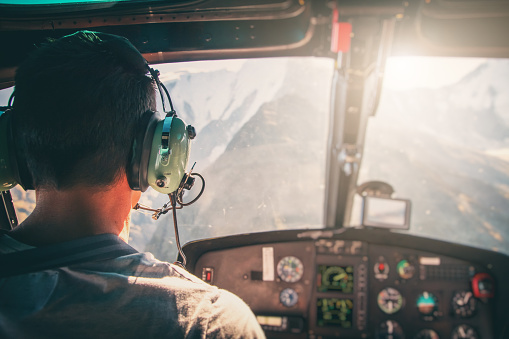 Helicopter cockpit with rear view of unrecognizable men co-pilot flying over Mont Blanc massif in French Alps mountains at sunset