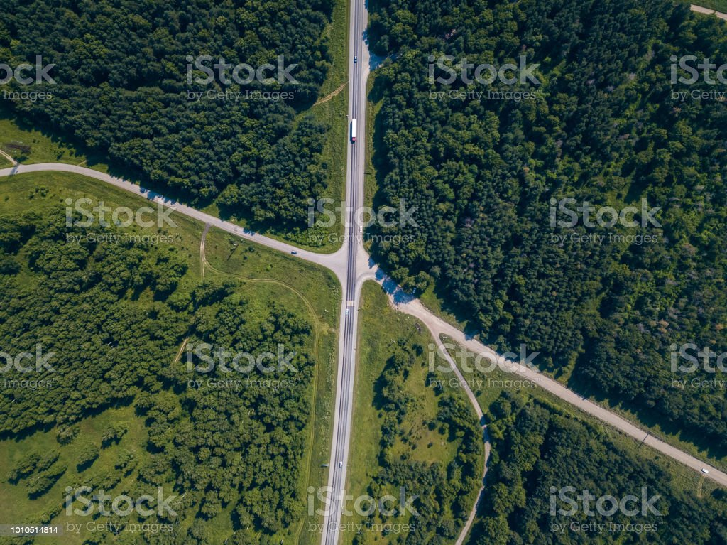 Helicopter drone shot. Aerial photography of green forest with road,...