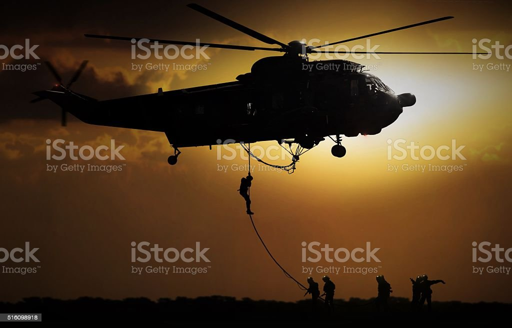 Helicopter dropping soldier during sunset stock photo