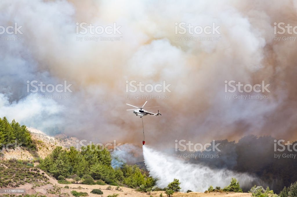 Helicopter dropping water for fire fighting Helicopter dropping water for fire fighting Accidents and Disasters Stock Photo