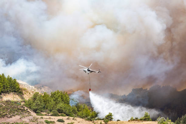 Helicopter dropping water for fire fighting stock photo