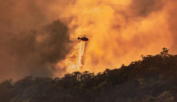 helicopter dumping water on forest fire - incendio boschivo foto e immagini stock