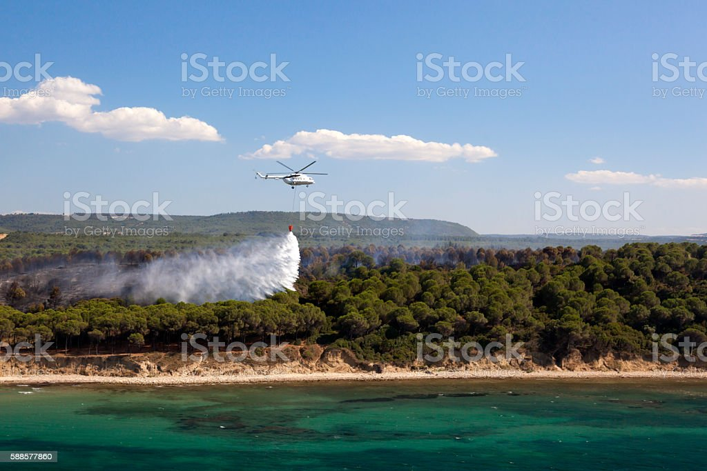 Helicopter extinguish a forest fire stock photo