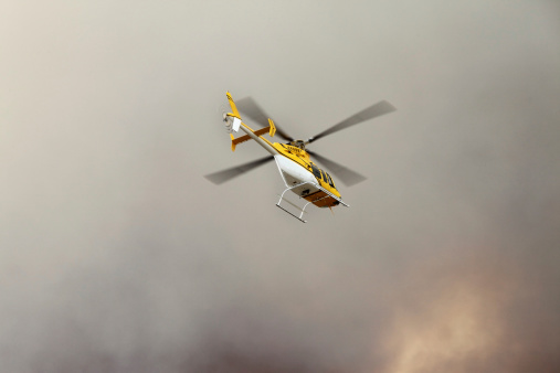 helicopter surveying a recently sparked wildfire in the California desert hills.