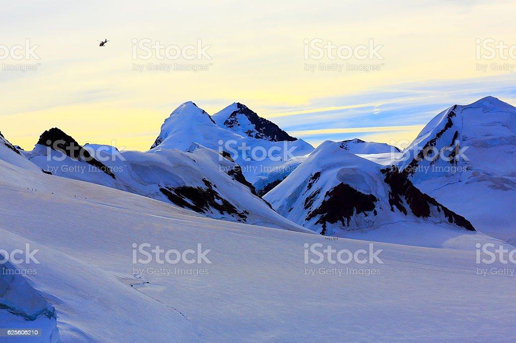 Helicopter flying above mountaineers hiking on Breithorn plateau – Swiss Alps stock photo