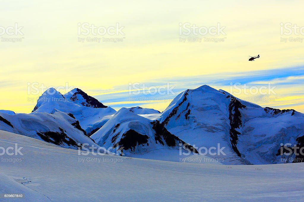 Helicopter flying above mountaineers hiking on Breithorn plateau, swiss alps stock photo