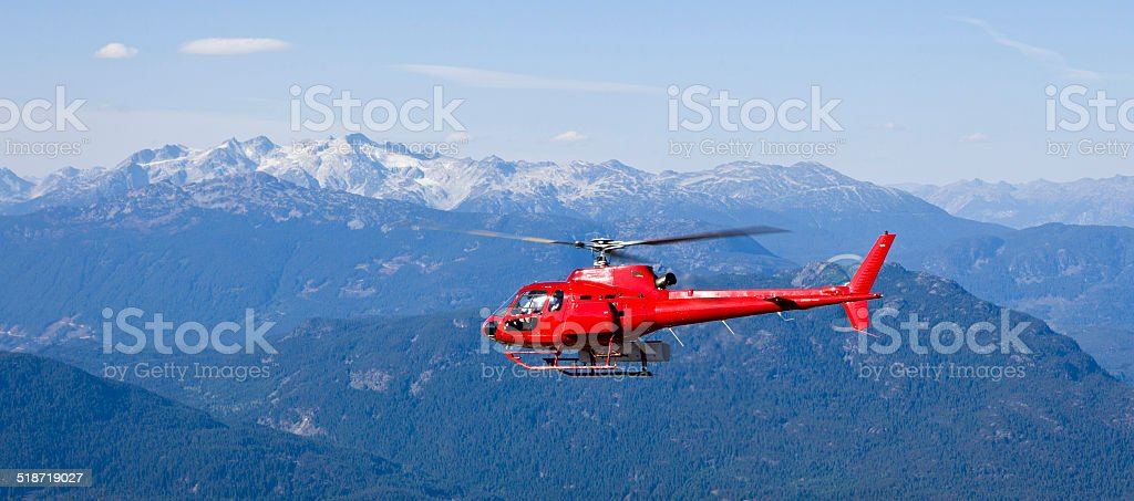 helicopter flying above mountains stock photo