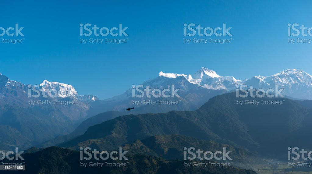 Helicopter flying among mountains, Pokhara, Nepal. stock photo
