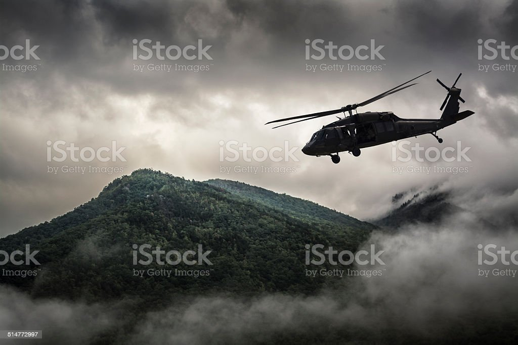 Helicopter Flying Over Mountain Surrounded by Fog stock photo