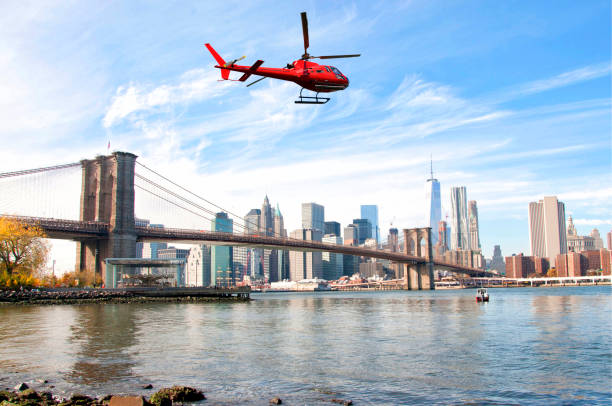 Helicopter flying over New York City skyscrapers and Brooklyn Bridge, USA stock photo