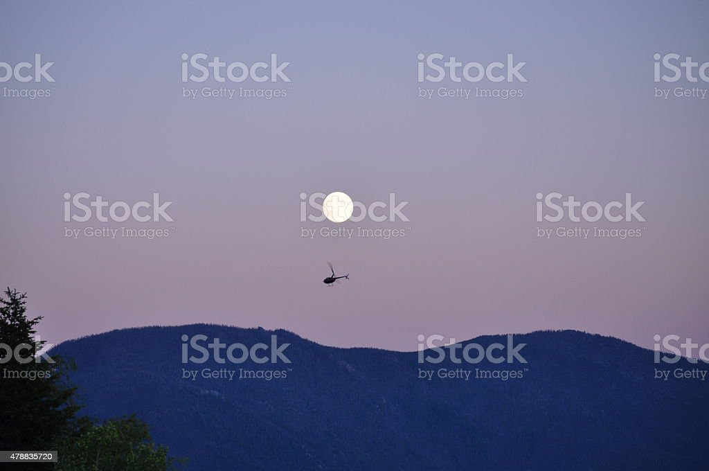 Helicopter Flying Over the East Ridge, Full Moon stock photo
