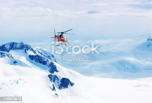 Helicopter flying over the mountains in Alaska, USA