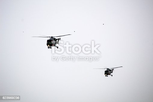 A twin formation of 2 Lynx helicopters flying low across a major UK airport.