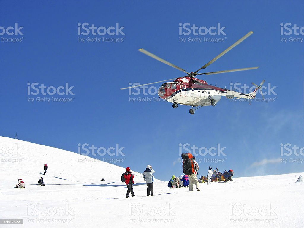 A helicopter hovering over a group of hikers on snow stock photo