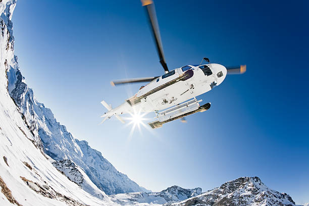 Helicopter in air above snow and mountains with sun stock photo
