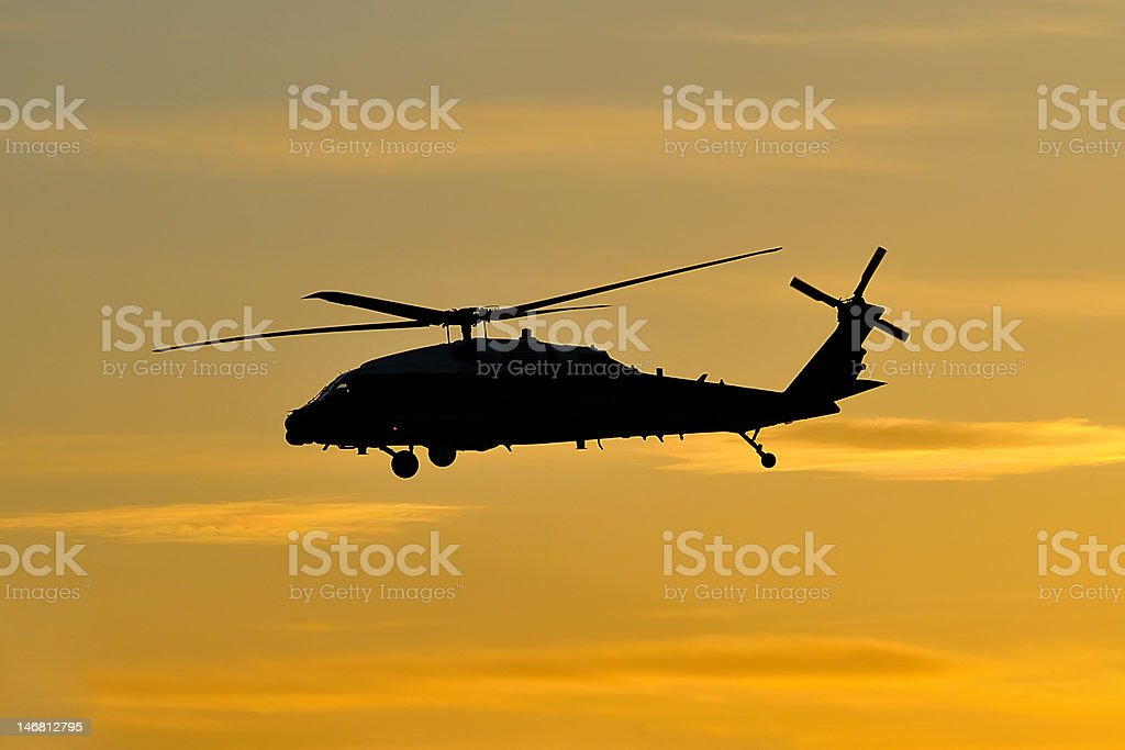 Helicopter in flight at sunset (silhouette) stock photo