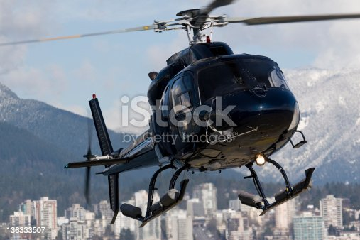 Dark blue helicopter on approach for landing with buildings and mountains in the background.