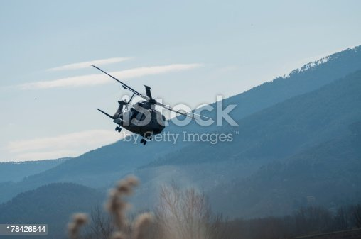Helicopter flying very low among the trees and fields