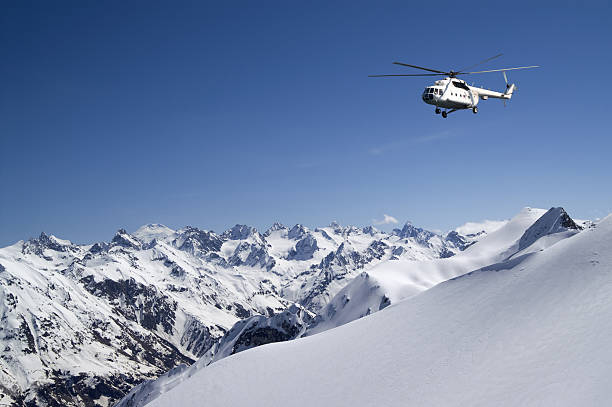 Helicopter in snowy mountains stock photo