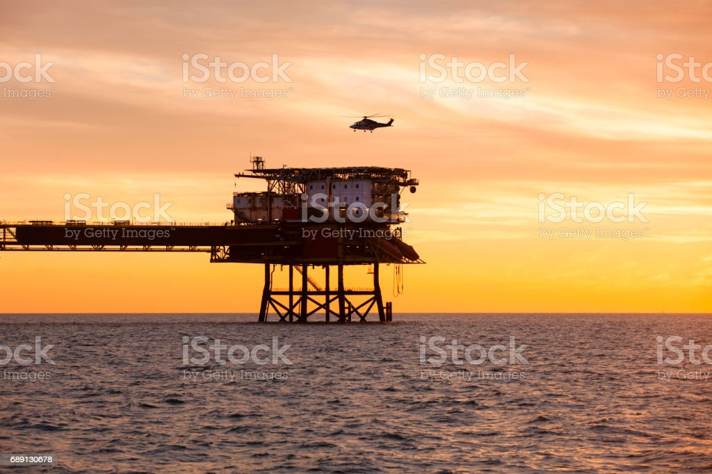 Helicopter is landing on an offshore oil installation during sunset stock photo