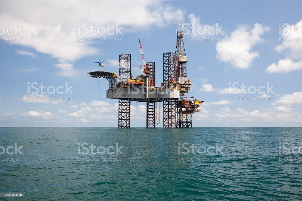 Helicopter is landing on the drilling rig stock photo