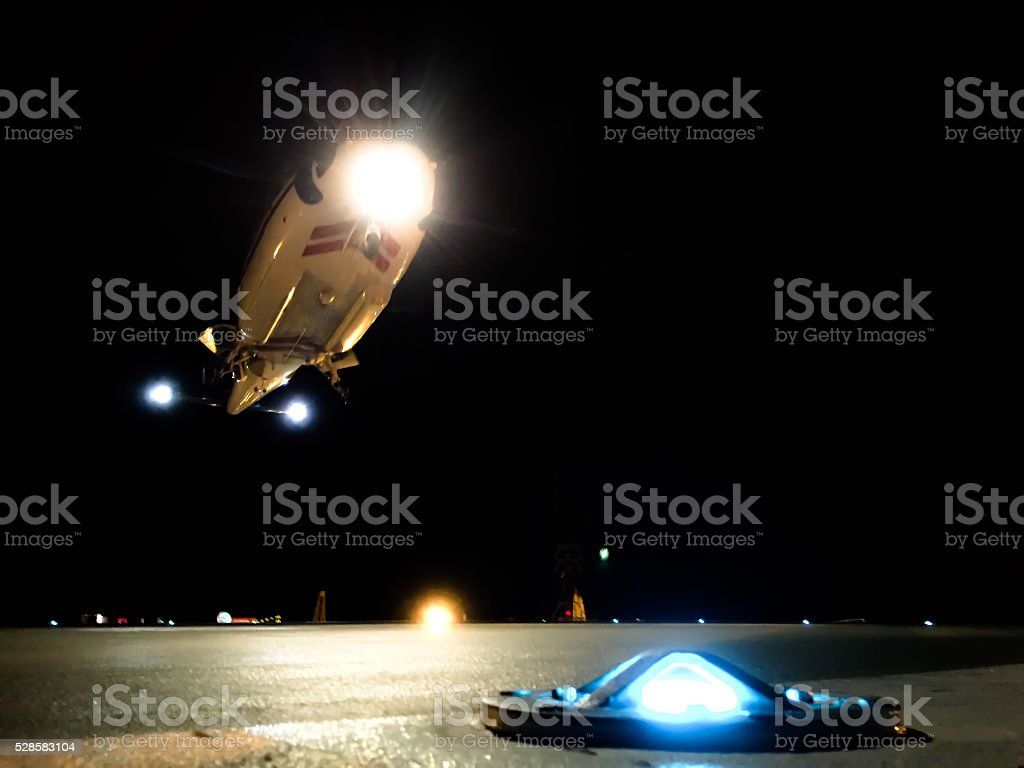 Helicopter landing at night on an offshore platform stock photo